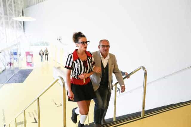 HuureenActeur actrice begeleidt bezoeker de trap op.